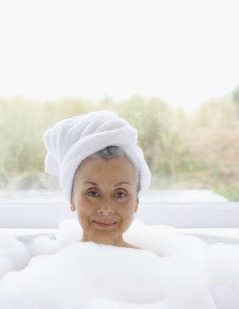 woman in bath: Portrait of elderly woman in bubble bath with towel wrapped around head