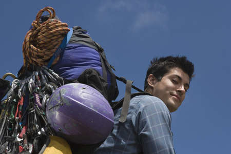 overburdened: Low angle portrait of man carrying backpack and equipment LANG_EVOIMAGES