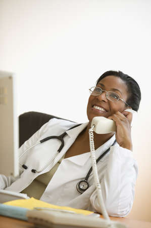 above 25: Female African American doctor sitting at desk and talking on phone