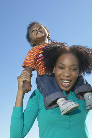 some under 18: Low angle view of woman with young son on shoulders LANG_EVOIMAGES