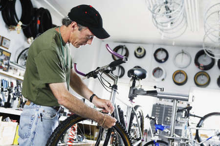 adult  body writing: Man repairing bike in bike shop