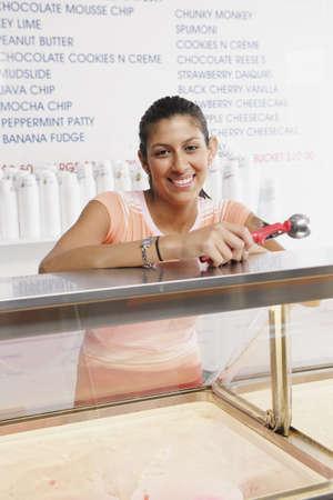 above 18: Portrait of teenage girl working in ice cream shop
