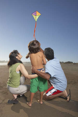 some under 18: Rear view of family flying kite at beach LANG_EVOIMAGES