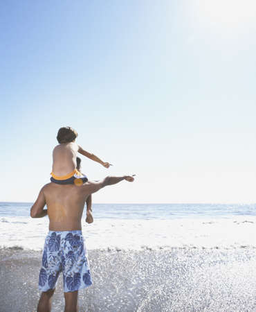 some under 18: Rear view of boy sitting on fatherís shoulders looking at ocean LANG_EVOIMAGES