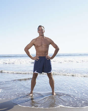 above 30: Full view of man standing with hands on hips at the beach