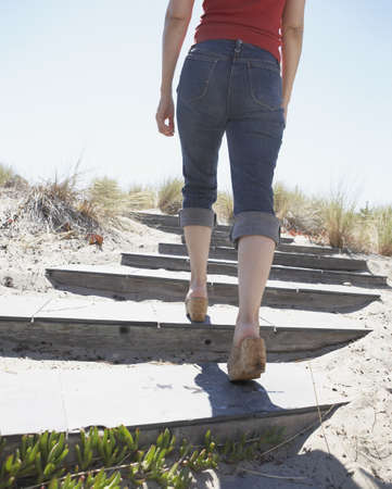 lower section view: Rear view of lower section of woman walking up stairs at beach LANG_EVOIMAGES