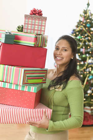 some under 18: Portrait of woman holding stack of gifts in front of Christmas tree