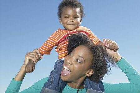 some under 18: Mother holding young son on shoulders LANG_EVOIMAGES