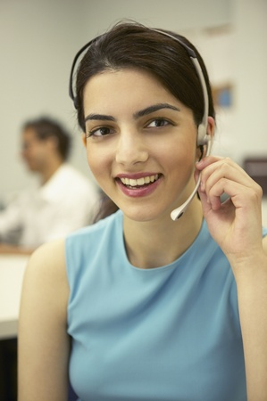 casualness: Young businesswoman talking on a headset