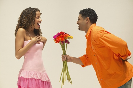 a meeting with a view to marriage: Young man giving girlfriend a bunch of flowers LANG_EVOIMAGES