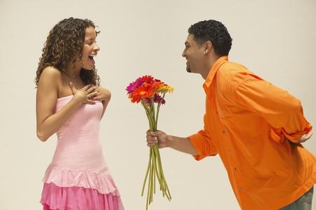 Young man giving girlfriend a bunch of flowers Stok Fotoğraf