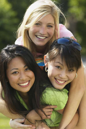 cherishing: Young women smiling together LANG_EVOIMAGES