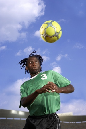 prevailing: Male soccer player headering the ball