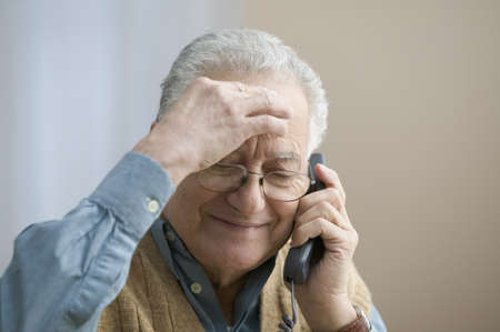 Older man rubbing his forehead as he talks on the telephone Stock Photo
