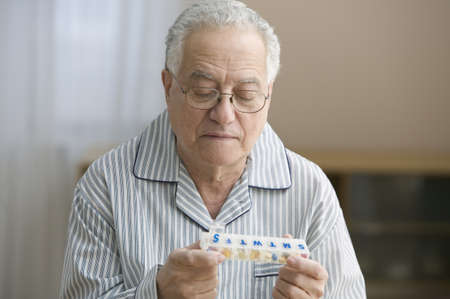 Older man examining pill cartridge