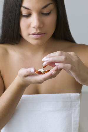 bathtowel: Young woman sorting out handful of pills