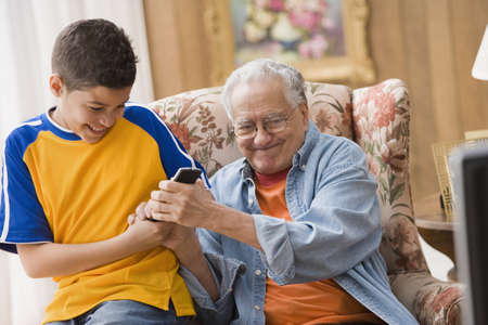 young boy: Young boy and his grandfather fighting over the remote control LANG_EVOIMAGES