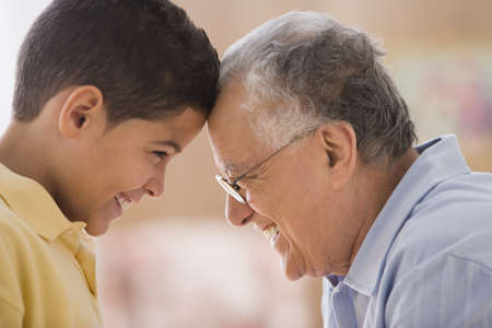 mischievious: Older man touching foreheads with his grandson