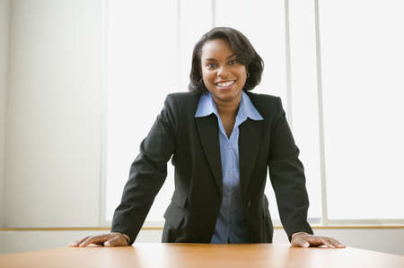 business woman: Businesswoman leaning over her desk