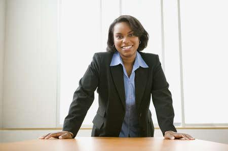 Unternehmerin lehnte über ihrem Schreibtisch
