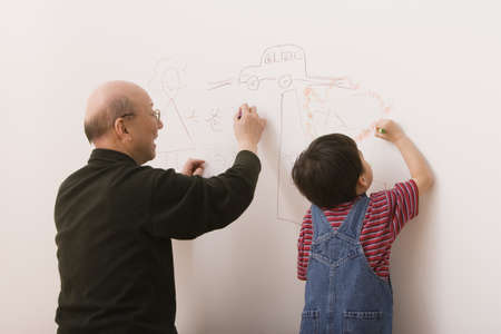 playing on divan: Elderly man and grandson drawing on the wall LANG_EVOIMAGES