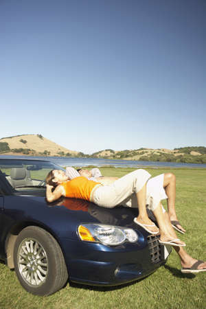 spare time: Couple relaxing on the hood of a convertible