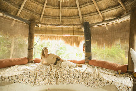 fathering: Young woman laying on bed in hut