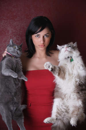 meanness: Young woman holding her cats