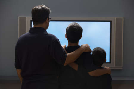 tv stand: Father and sons watching a widescreen television