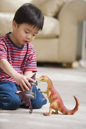 playing on divan: Young boy playing with toy dinosaurs