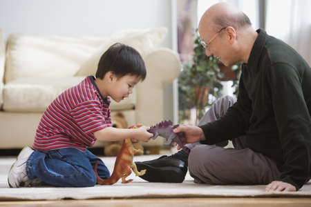 thirty's: ELderly man and grandson playing with toy dinosaurs