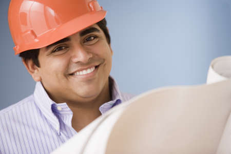 thirtys: Construction worker wearing a hard hat while looking at blueprints
