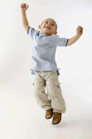 bambino: Young boy jumping for joy