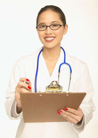 toiling: Young female doctor smiling for the camera while holding clipboard