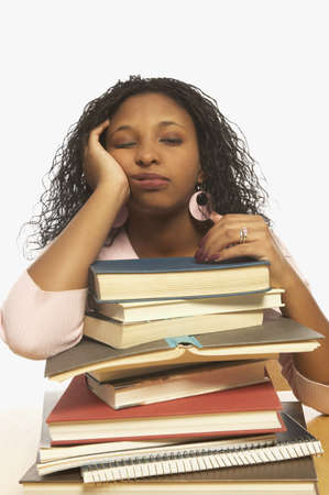 wearying: Young woman sleeping on a pile of books LANG_EVOIMAGES