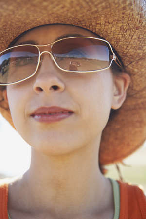 Young woman wearing sunglasses and a straw hat Stock Photo