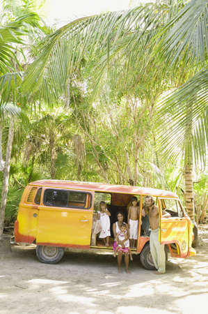age 5: Family posing for the camera with van in tropical setting