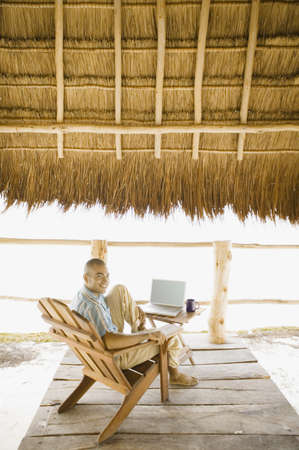toiling: Young man using a laptop underneath thatch roof on the beach LANG_EVOIMAGES
