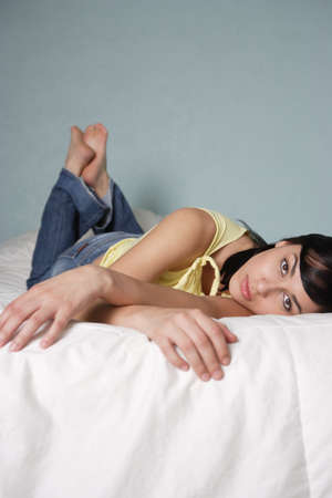 tiresome: Young woman posing for the camera on her bed LANG_EVOIMAGES