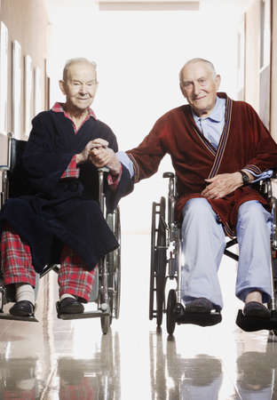 Elderly men smiling for the camera in wheelchairs
