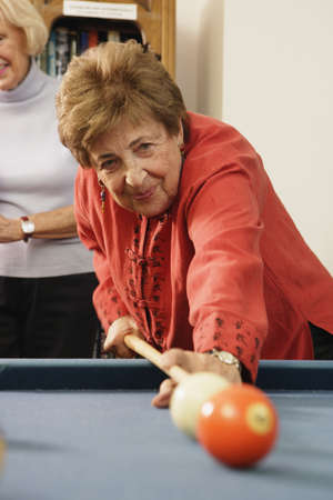 Elderly woman shooting pool