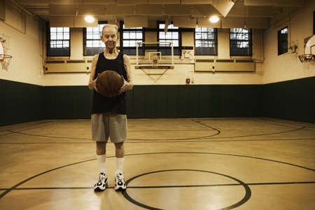 Elderly man standing in basketball court