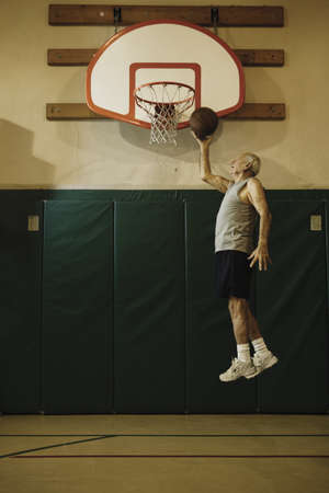 Elderly men jumping to slam dunk a basketball Stock Photo