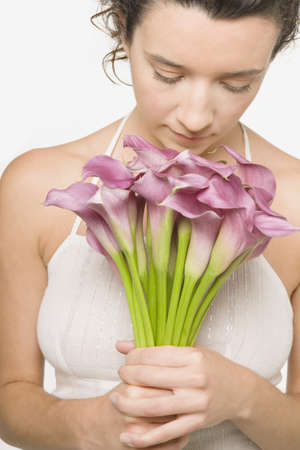 lower section view: Young woman smelling a bunch of flowers LANG_EVOIMAGES