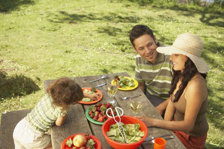poppa: Family eating on a picnic table outdoors
