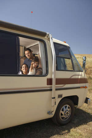 adventuresome: Family looking out of recreational vehicle window LANG_EVOIMAGES