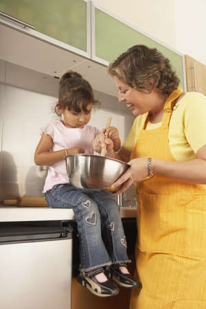 attentiveness: Mother and daughter cooking together