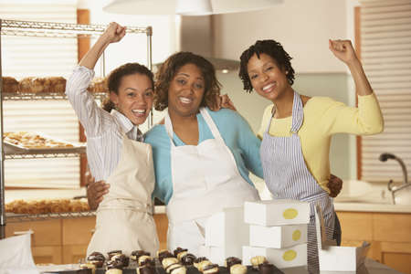attentiveness: Portrait of three woman cheering while working in bakery