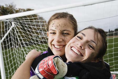 soccer net: Two girls hugging in front of soccer net