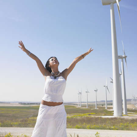 above 25: Young woman with outstretched arms by wind turbines